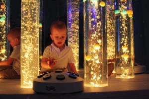 JENNIFER CORBETT/The Kentucky Standard Brayden Reiter, 5, presses a button to change the bubble tubes in Bardstown Primary's new Snoezelen Room from yellow to orange.